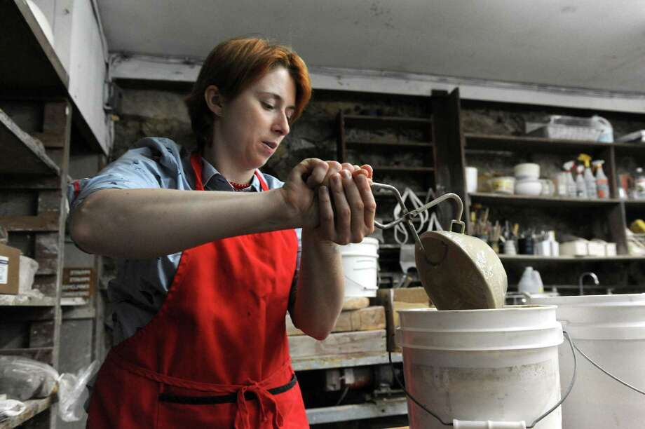 Stephanie Fuda, 36, of Danbury, dips her ceramic piece into a bucket of glaze at a pottery course at the Brookfield Craft Center. (File photo Wednesday, August 12, 2015.) Photo: Carol Kaliff / Hearst Connecticut Media / The News-Times