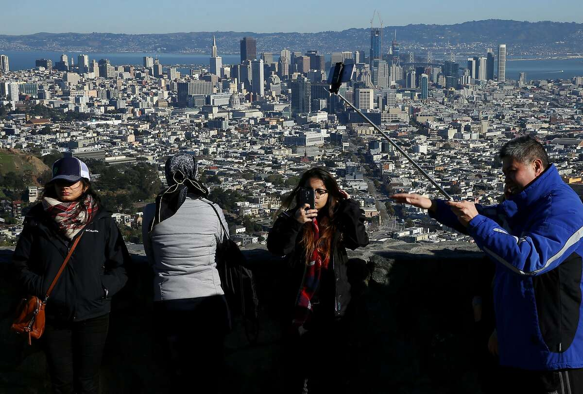 Visitors check out the view from Twin Peaks and snap pictures on their smartphones and selfie sticks on Wednesday, Dec. 28, 2016 in San Francisco, Calif.