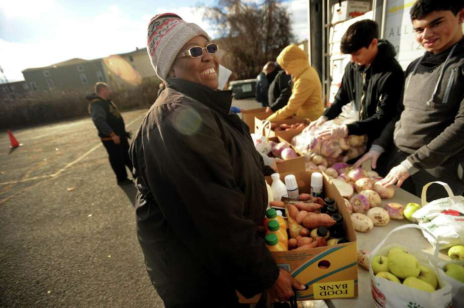 Ketena Charles, of Bridgeport, smiles as she carries a box of food from the Monthly Mobile Food Pantry on Jane Street in Bridgeport, Conn. on Wednesday, December 28, 2016. The pantry is staffed by three groups of volunteers making up The Emmaus Partnership. Photo: Brian A. Pounds / Hearst Connecticut Media / Connecticut Post