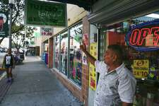 Perfume King owner Suresh Mansinghani points to a sign he put up outside his store advertising a better exchange rate for the peso. Mexican shoppers, who make up 95 percent of his customer base, consider perfume a staple, not a luxury, and he thinks they'll keep coming despite the drop in the peso's value.