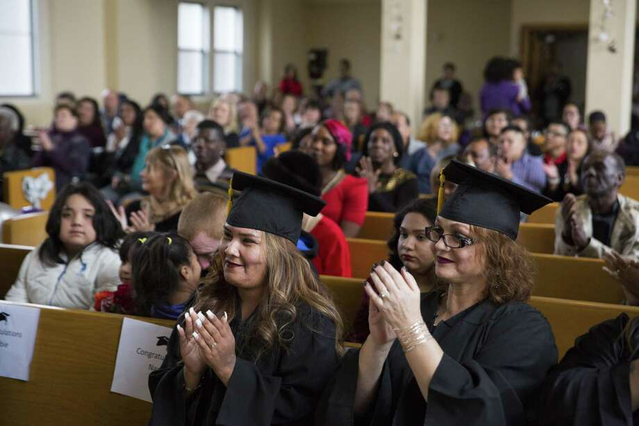 Teresa R., left, and Lorretta M., right, clap for a fellow graduate during a graduation ceremony for the first group of women to complete the two year Esperanza Court program on December 9, 2016 at Crosspoint Chapel in San Antonio, Texas. Esperanza Court, one of the specialty treatment courts serving the Bexar County District Courts, is a felony court that focuses on individuals with three or more convictions for prostitution. Photo: Carolyn Van Houten /Carolyn Van Houten / 2016 San Antonio Express-News