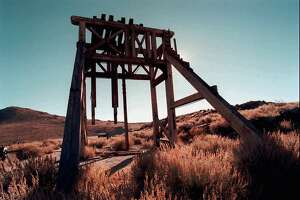 APN ADVANCE FOR SUNDAY, NOV 23--A head frame sits atop a mine shaft in the gold-mining ghost town of Bodie, Calif., Oct. 18, 1997. The infamous ghost town won't be distrupted by renewed mining, thanks to a $5 million government buyout of old claims. The combination state and federal buyout has doubled the size of Bodie State Historic Park to more than 1,000 acres.  Thus, Bodie will remain undisturbed, except by the 200,000-plus tourists who come here each year. The idea, when it became a state park 35 years ago, was to leave it in a state of 'arrested decay,' frozen in time.  (AP Photo/Nevada Appeal, K.M. Cannon)