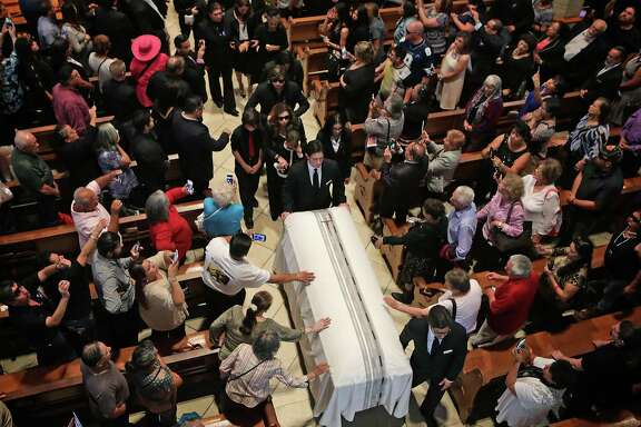 Mourners reach to touch the casket of Emilio Navaira as it leaves the funeral service, and Mass celebrated by Archbishop Gustavo Garcia-Siller, at San Fernando Cathedral on Monday, May 23, 2016.