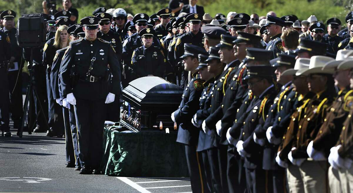 Police officers stand at attention as San Antonio Police Honor Guard prepare to carry the coffin of Detective Benjamin Marconi during his funeral service at Community Bible Church on Monday, Nov. 28, 2016.