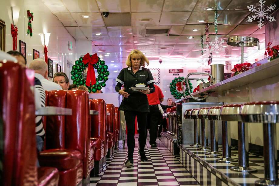 Marta Delfino, a waitress of over 25 years, walks through Lori's Diner on Mason Street as she serves food in San Francisco, Calif., on Wednesday, Dec. 28, 2016. Lori's Diner in Union Square will be closing after 32 years. Photo: Gabrielle Lurie, The Chronicle