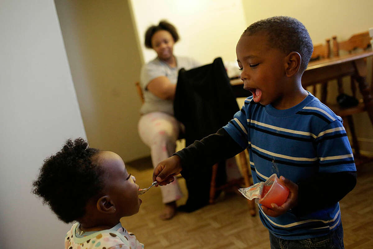 Edward Brown Jr., once stricken with lead poisoning so severe he was hospitalized, feeds his sister Jewel, 1, at their home in South Bend, Indiana. His mother, Victoria Marshall, said Edward's health has improved but she remains worried about lead's lasting impact.