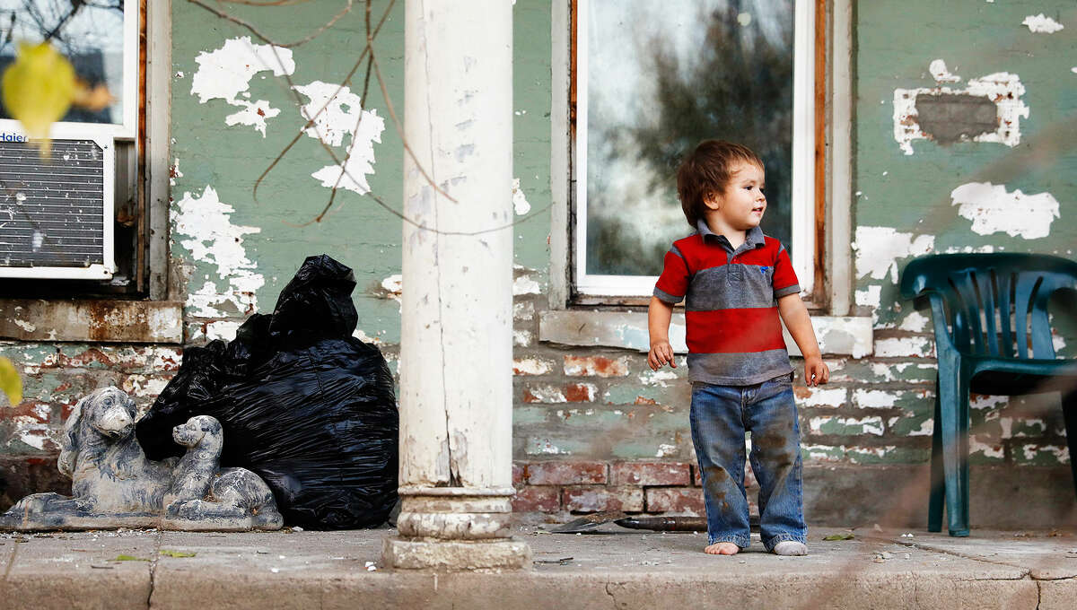 St. Joseph, Missouri, has neighborhoods filled with aged homes and high rates of lead poisoning. Here, Kadin Mignery, 2, plays on his front porch. Kadin was diagnosed with lead poisoning, prompting his mother to change his diet and repaint the home's interior.