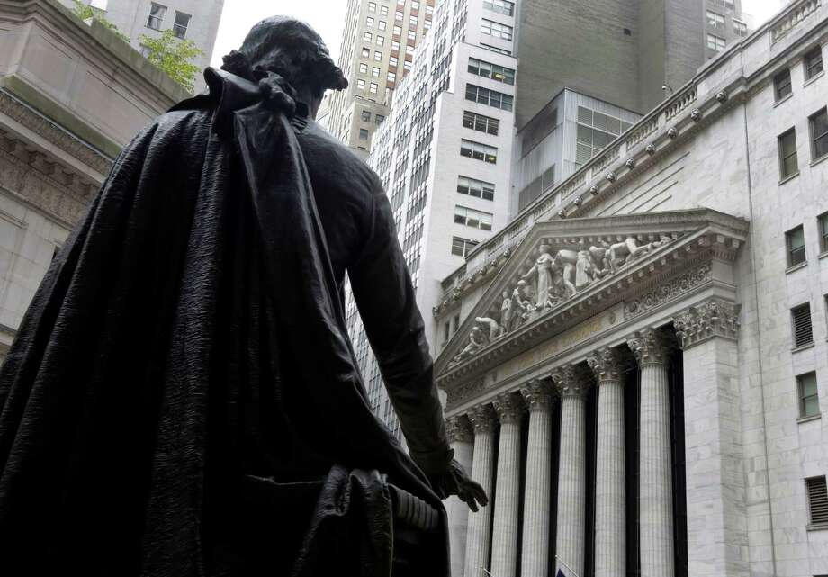 A statue of George Washington faces the facade of the New York Stock Exchange. After a tumultuous 2016, experts expect 2017 to see a good job market and a slight rise in gas prices. Photo: Richard Drew, STF / Copyright 2016 The Associated Press. All rights reserved. This material may not be published, broadcast, rewritten or redistribu