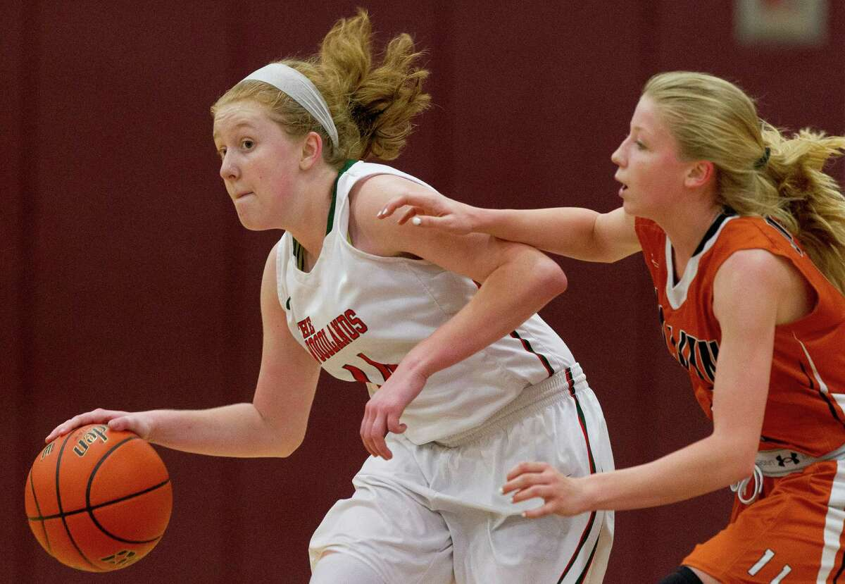 The Woodlands forward Emma Warnsman (14) drives past Alvin guard Andreea Mancha (1) during the third quarter of a high school girls basketball game at the Magnolia Holiday Hoop Fest Wednesday, Dec. 28, 2016, in Magnolia. The Woodlands defeated Alvin 43-28.