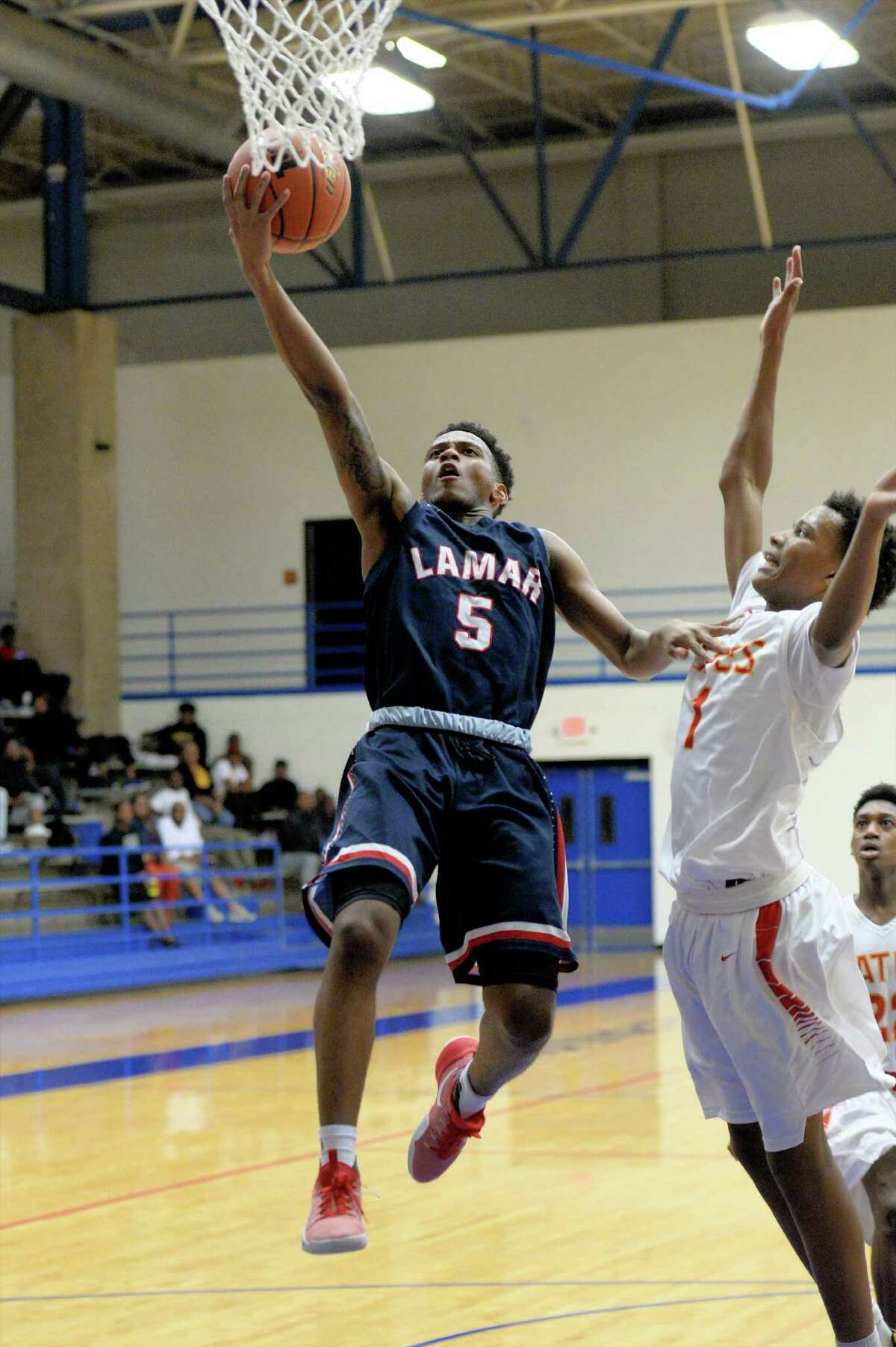 Tamir Bynum (5) of Lamar drives to the hoop during the first half of a boys basketball game between the Lamar Texans and the Yates Lions at the Houston ISD Tournament on Saturday December 17, 2016 at The Pavilion, Houston, TX.