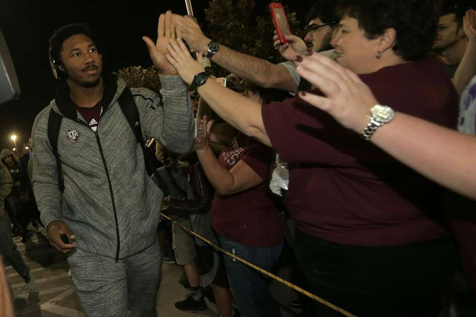 Texas A&M defensive lineman Myles Garrett (15) high fives fans as he makes his way to the stadium before the start of the Advocare V100 Texas Bowl at NRG Stadium on Wednesday, Dec. 28, 2016, in Houston. ( Elizabeth Conley / Houston Chronicle )