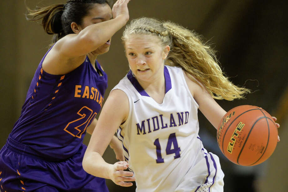 Midland High's Taysha Rushton (14) moves the ball against El Paso Eastlake's Jeannine Gonzalez (21) during the first round of the Byron Johnston Holiday Classic on Wednesday, Dec. 28, 2016, at Chaparral Center.  James Durbin/Reporter-Telegram Photo: James Durbin