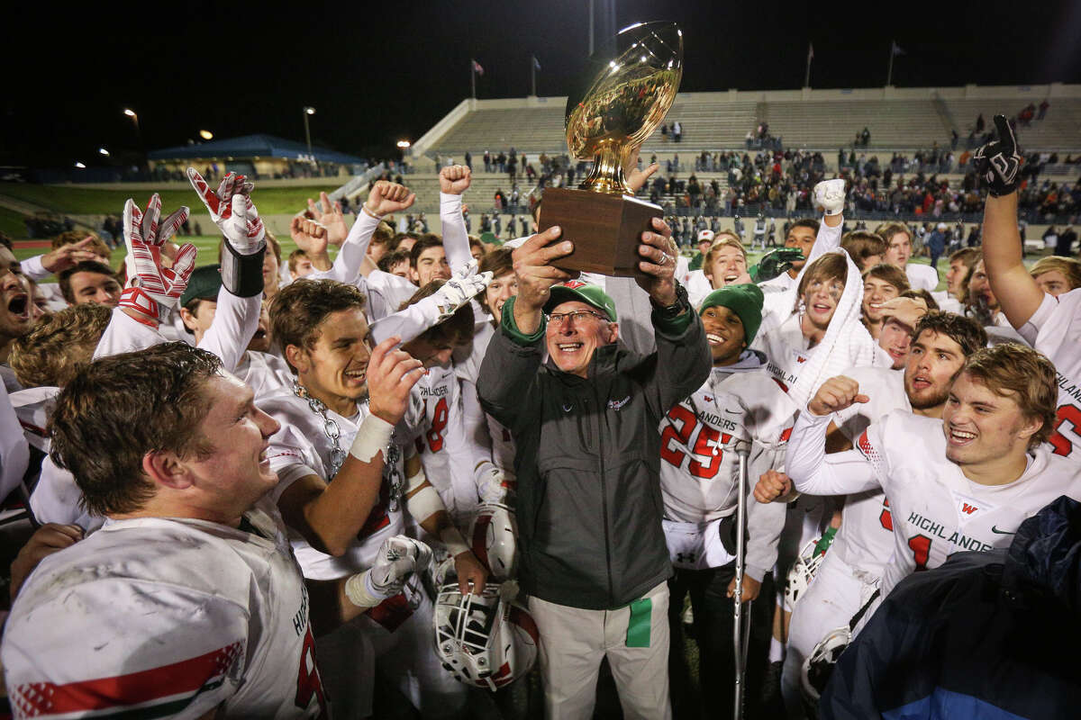 The Woodlands head coach Mark Schmid lifts a trophy after the Highlanders won an area round playoff game against Sachse on Friday, Nov. 18, 2016, in Waco, Texas. (Michael Minasi / Chronicle)