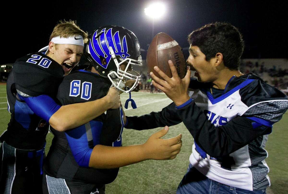 New Caney's Mason Vaughn (20) hugs kicker Jason Gonzalez (60) as he is presented with the game ball after kicking 26-yard field goal to give the Eagles a 31-28 triple-overtime win over Beaumont Central in a Region III-5A Division 1 bi-district high school football game at Turner Stadium Saturday, Nov. 12, 2016, in Humble.