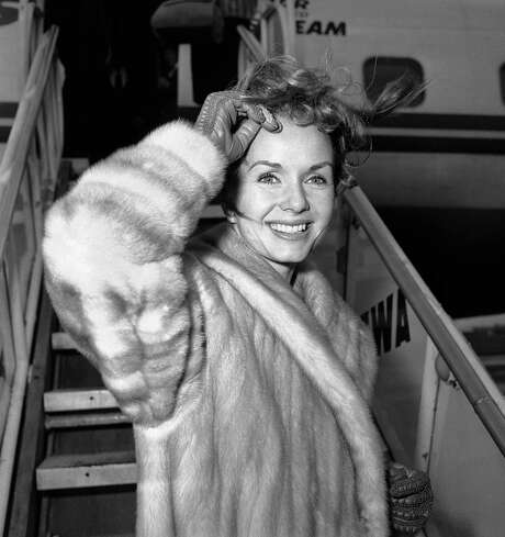 "FILE- In this March 6, 1959, file photo actress Debbie Reynolds boards an airliner in New York en route to Spain where she will film a new picture. Reynolds, star of the 1952 classic ""Singin' in the Rain"" and mother of Carrie Fisher, died Wednesday, Dec. 28, 2016, according to her son Todd Fisher. She was 84. (AP Photo/John Rooney, File) Photo: John Rooney, STF / AP1959"