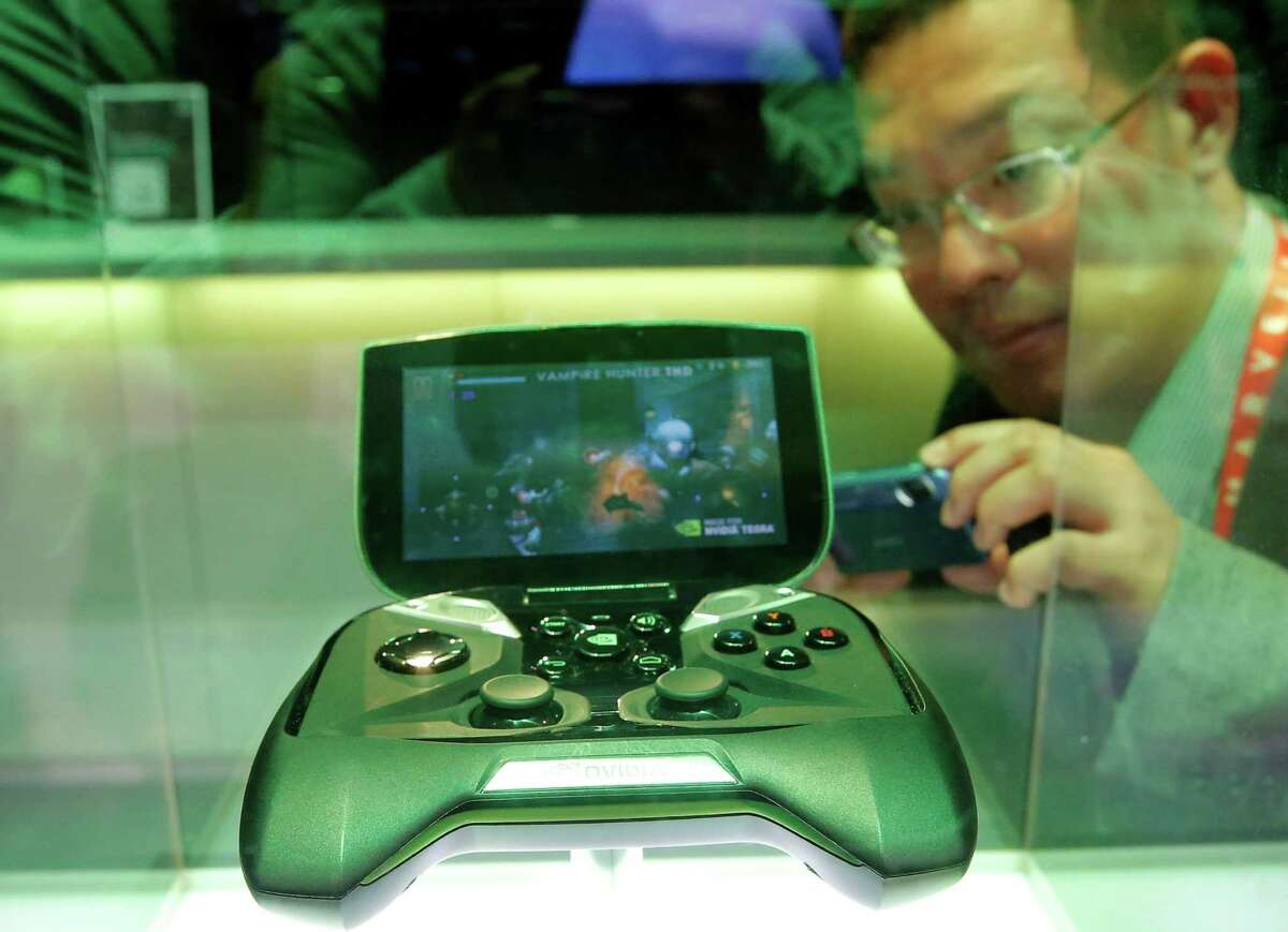 FILE - In this Tuesday, Jan. 8, 2013, file photo, Nvidia's portable handheld gaming device, the Project Shield, is on display at the company's booth at the International Consumer Electronics Show in Las Vegas. Chipmaker Nvidia more than tripled in value in 2016, far more than any other company on the S&P 500. (AP Photo/Jae C. Hong, File) ORG XMIT: NYBZ301