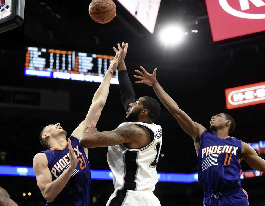 LaMarcus Aldridge of the San Antonio Spurs shoots and scores against Alex Len, left, and Brandon Knight (11), of the Phoenix Suns during second-half NBA action at the AT&T Center on Wednesday, Dec. 28, 2016. Photo: Billy Calzada, Staff / San Antonio Express-News / San Antonio Express-News