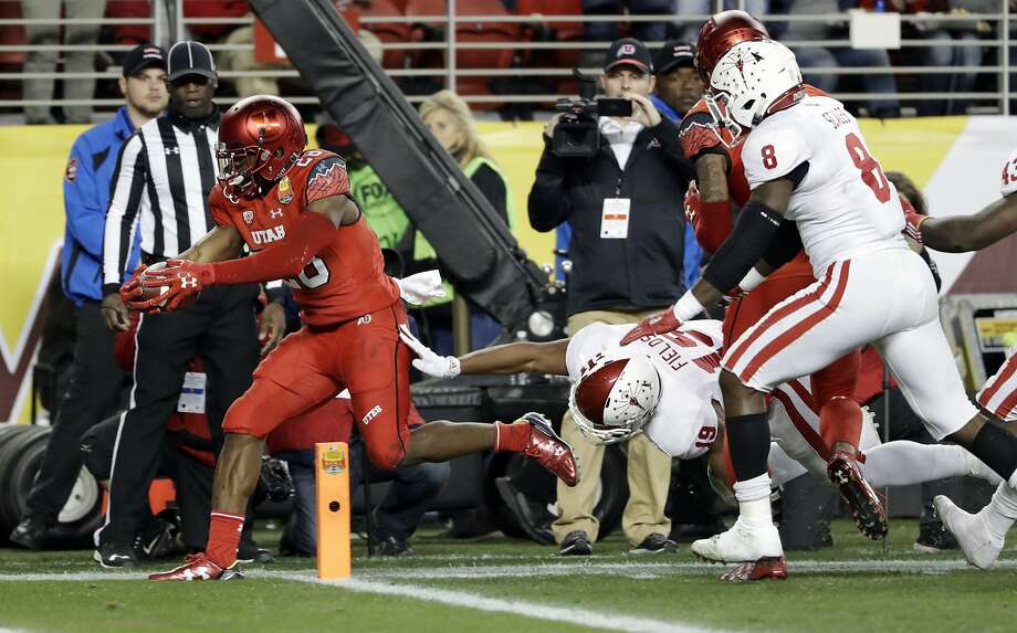 Utah running back Joe Williams, left, scores against Indiana during the first half of the Foster Farms Bowl NCAA college football game Wednesday, Dec. 28, 2016, in Santa Clara, Calif. (AP Photo/Marcio Jose Sanchez) Photo: Marcio Jose Sanchez, Associated Press