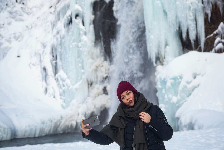 Tatsiana Yaromich takes a selfie at a frozen Franklin Falls near Snoqualmie Pass on Wednesday, Dec. 28, 2016.