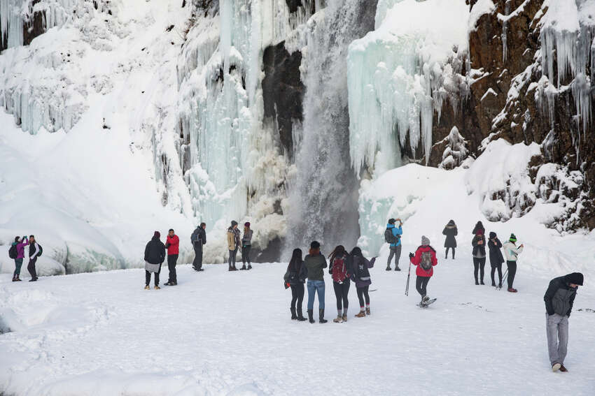 Hikers hang at a frozen Franklin Falls near Snoqualmie Pass on Wednesday, Dec. 28, 2016.