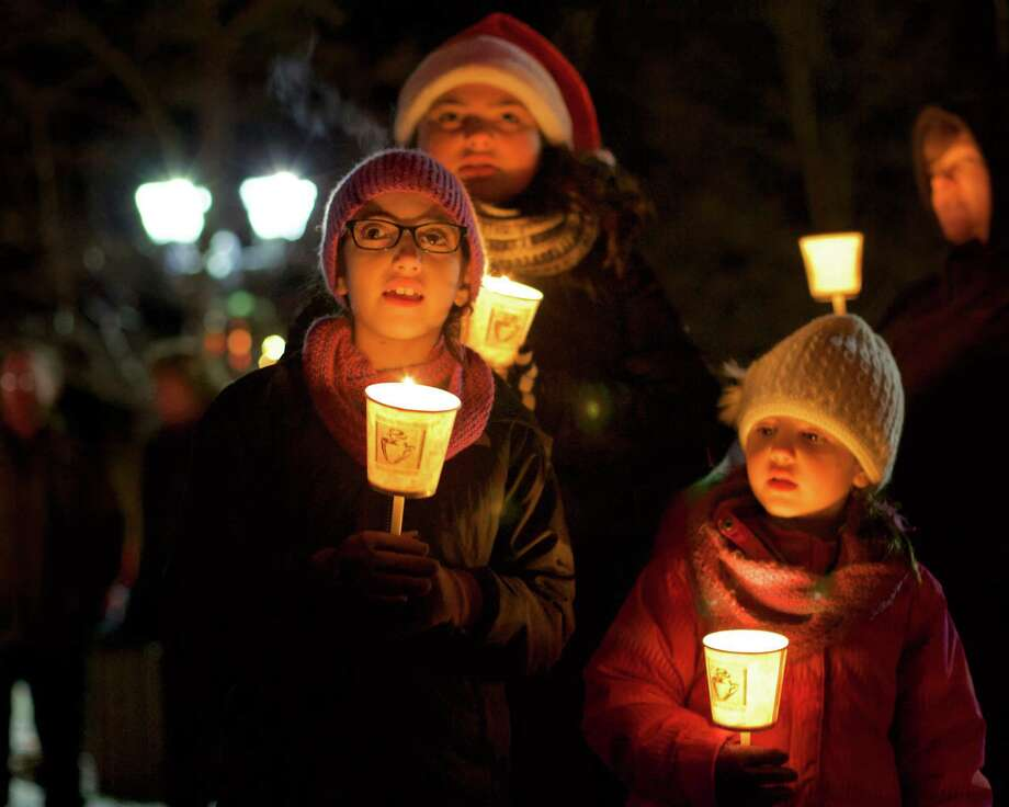"""Singing """"Joy to the World"""" during the annual Carol Sing in New Milford are, from left to right, Ava Morais, 8, of Danbury, Julisa Peralta, 11, of New Milford, and Alexa Morais, 5, of Danbury. Photo: Trish Haldin / / The News-Times Freelance"""