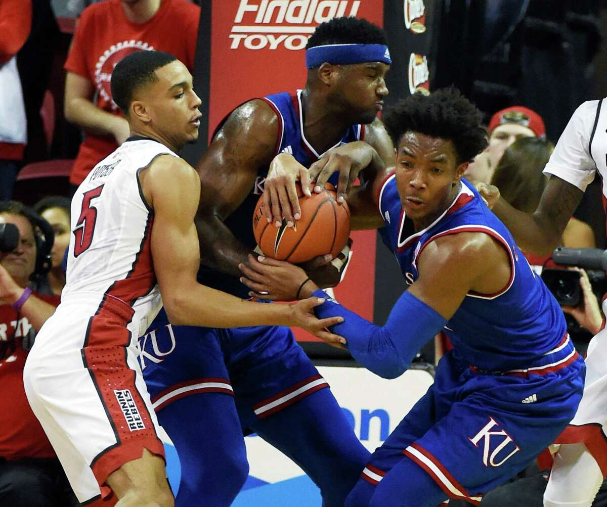 LAS VEGAS, NV - DECEMBER 22: (L-R) Jalen Poyser #5 of the UNLV Rebels and Carlton Bragg Jr. #15 and Devonte' Graham #4 of the Kansas Jayhawks fight for a rebound during their game at the Thomas & Mack Center on December 22, 2016 in Las Vegas, Nevada. Kansas won 71-53.