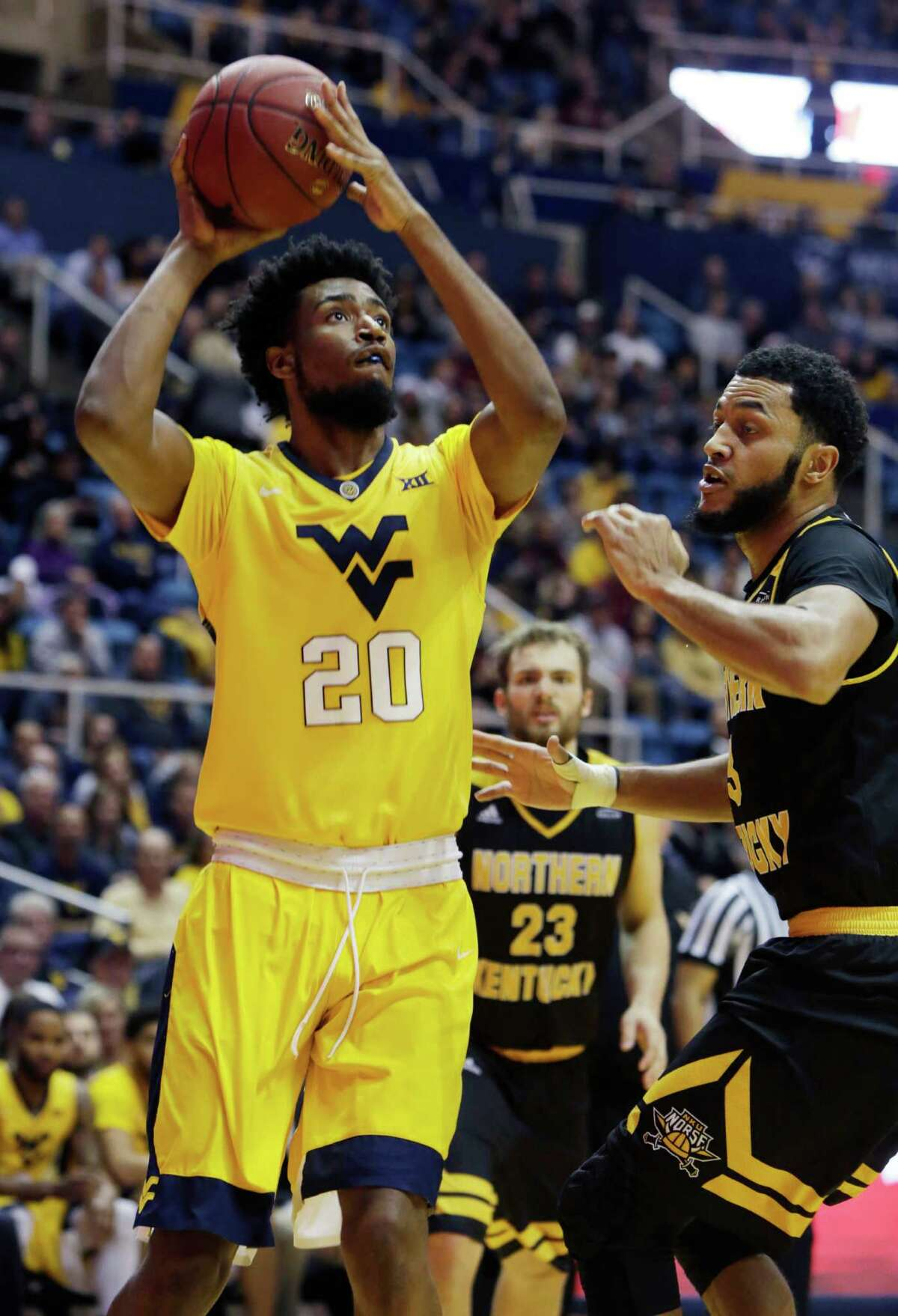 West Virginia forward Brandon Watkins (20) takes a shot while being defended by Northern Kentucky forward Brennan Gillis (13) during the second half of an NCAA college basketball game, Friday, Dec. 23, 2016, in Morgantown, W.Va. West Virginia defeated Northern Kentucky 92-61. (AP Photo/Raymond Thompson)