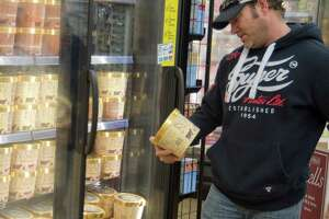 Steve Morris decides on a tub of Homemade Vanilla Blue Bell Monday 12-14-2015 after the ice cream was restocked on Midland shelves early Monday at Market Street. Tim Fischer\Reporter-Telegram