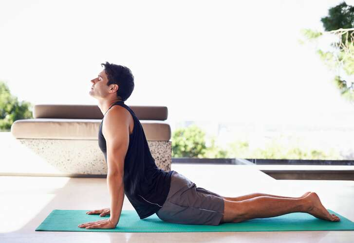 A side view shot of a content young man doing yoga at homehttp://195.154.178.81/DATA/i_collage/pi/shoots/783553.jpg   a