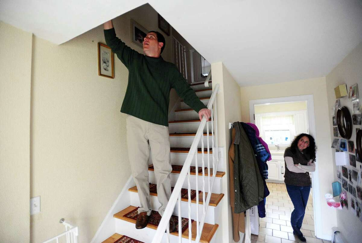 Safer Alarms Inc. founder and CEO Marc Toland sticks one of his prototype alarms on the wall while his wife looks in their Stamford home Wednesday.