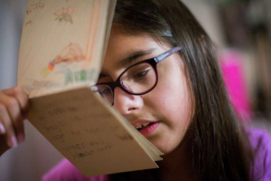 Sophia Salehi, 9, gets close to read an illustrated story she wrote and illustrated. Salehi is legally blind but she was denied special education services by Houston Independent School District. Photo: Marie D. De Jesus, Houston Chronicle / © 2016 Houston Chronicle