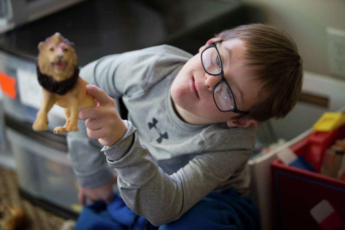 Sam Bullion, 10, plays with animal toy figures at his home in Austin. Bullion was born with Down syndrome, but his mother had to struggle to get him into special education.