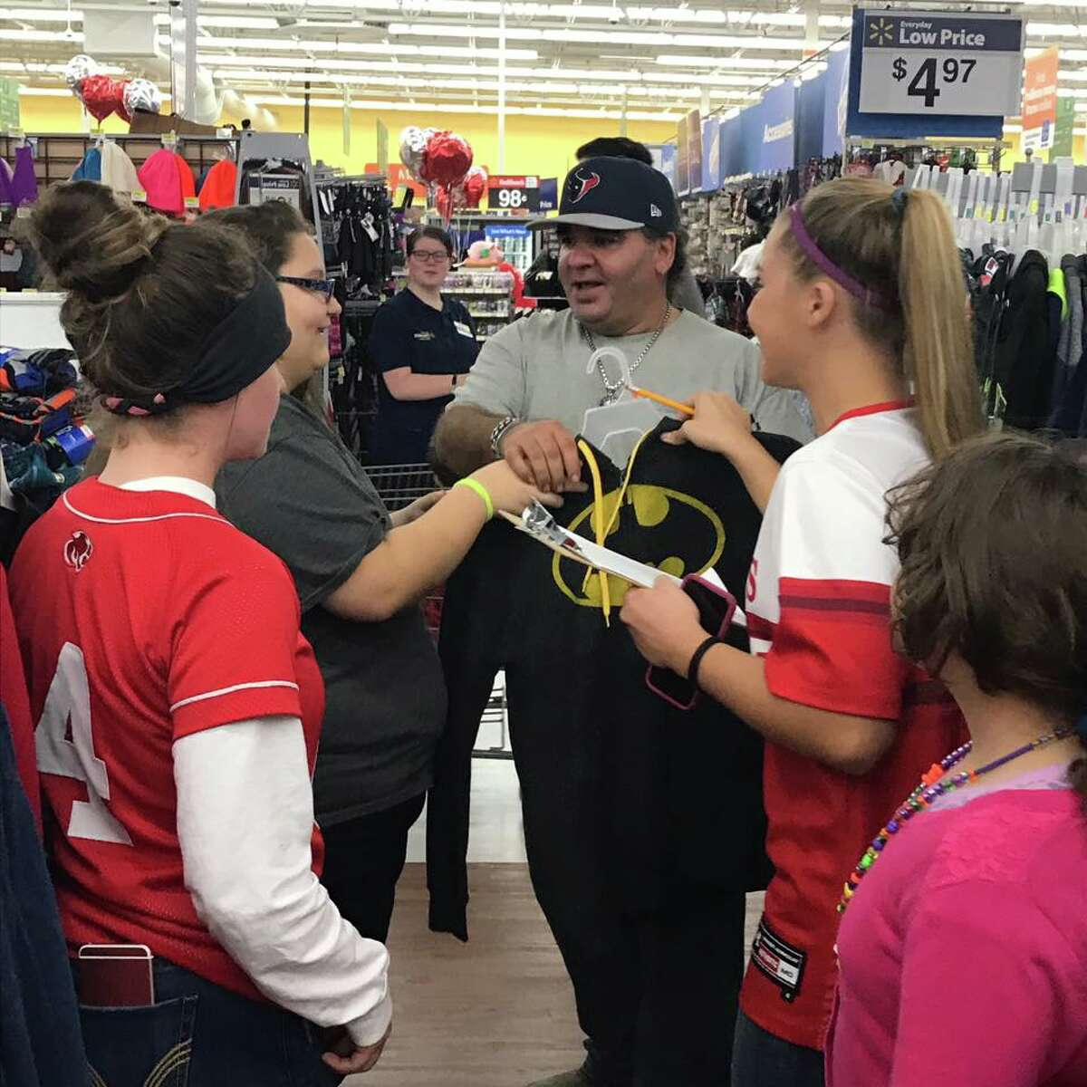 Baseball and softball players from Crosby Independent School District help children pick out clothes during this year's annual Clothe-A-Child drive hosted by Crosby Cares. More than 300 students from the area benefited from the event.