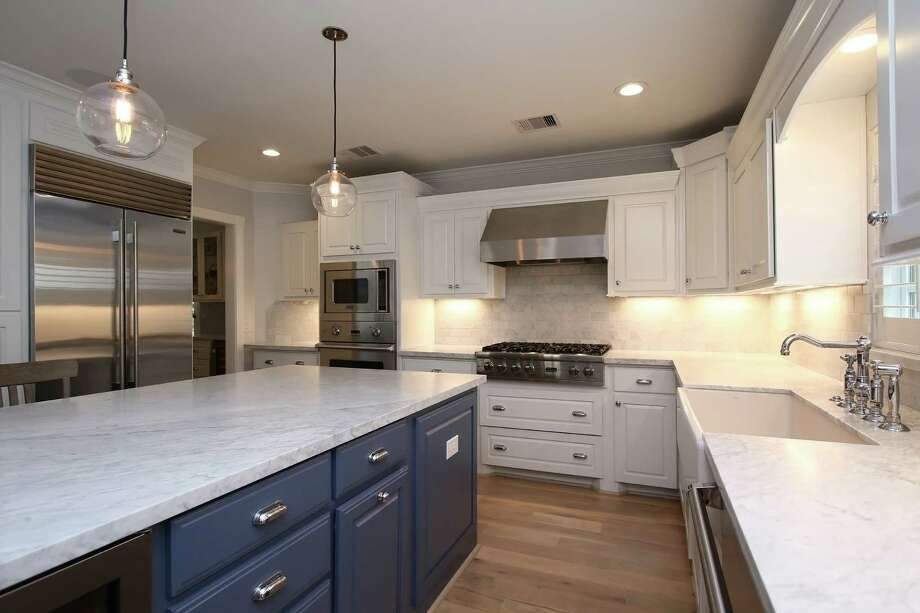 White paint provides an instant facelift for kitchen cabinets, but you can also go with two colors. Use one for upper and another for lower cabinets, or use one on main counters and a different color on an island. Photo: Courtesy Of Remodelers Of Houston