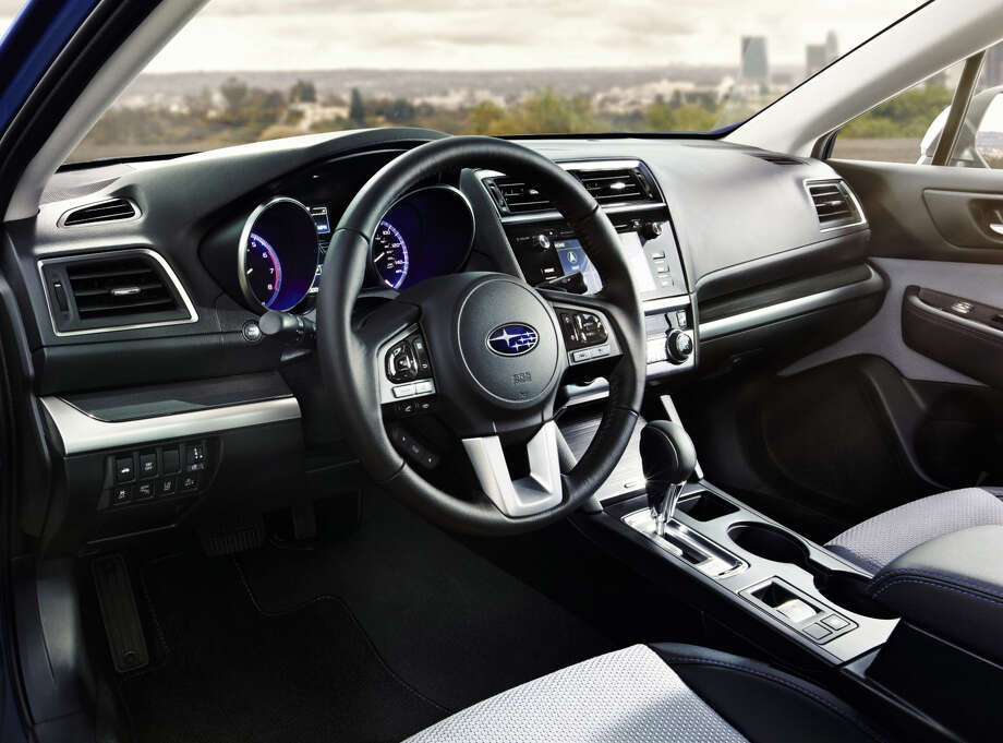 The Legacy 2.5i Sport can be distinguished by its standard cloth interior with blue stitching, gloss black and faux carbon fiber trim, leather-wrapped steering wheel and auto-dimming rearview mirror with compass and Homelink. Photo: Subaru