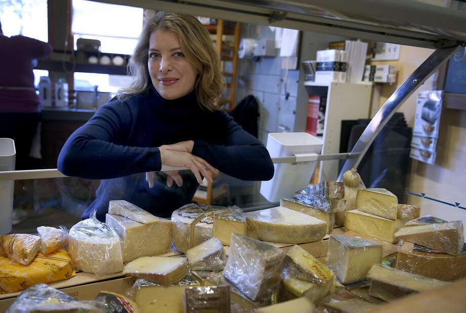 "Nina Teicholz, above, at the cheese counter at the Cheese Board Collective in Berkeley, is the author of ""The Big Fat Surprise,"" which concludes that saturated fats, including cheese, left, actually lead to better health. Photo: Paul Chinn, The Chronicle"