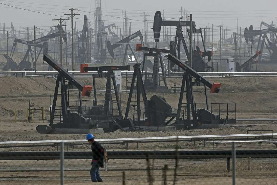 In this January 2015 file photo, a person walks past pump jacks operating at the Kern River Oil Field in Bakersfield, Calif. Credit: Jae C. Hong/Associated Press.