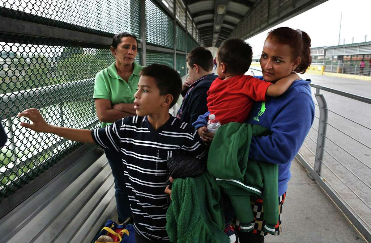 Alejandra Flores, right, from Honduras, huddles with her sons Alexande Josue Romero, 3, and Brision Josue Romero, 10, left, with other immigrants on the Hidalgo International Bridge in the early hours on Tuesday, Dec. 27, 2016, hoping to be let in the U.S. after a 22 day journey from their home in Honduras, spending Christmas on the road.