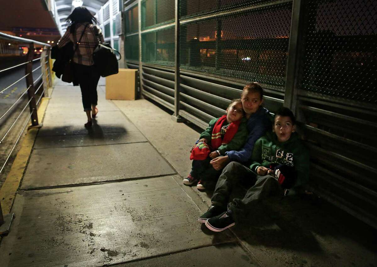 Alejandra Flores, from Honduras, huddles with her sons Alexande Josue Romero, 3, and Brision Josue Romero, 10, on the Hidalgo International Bridge in the early hours on Tuesday, Dec. 27, 2016, hoping to be let in the U.S. after a 22 day journey from their home in Honduras, spending Christmas on the road.