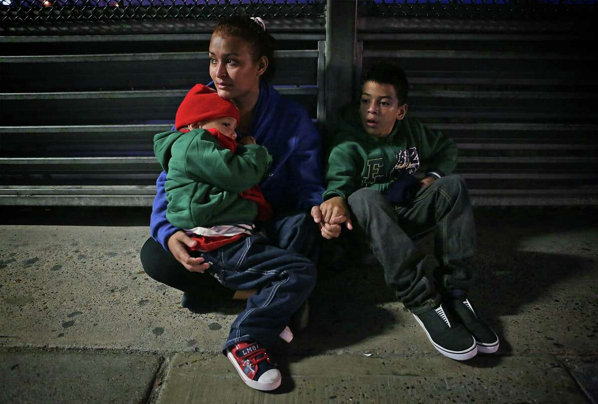 Fighting back tears, Alejandra Flores, from Honduras, clutches her sons Alexande Josue Romero, 3, and Brision Josue Romero, 10, on the Hidalgo International Bridge in the early hours on Tuesday, Dec. 27, 2016, hoping to be let in the U.S. after a 22 day journey from their home in Honduras, spending Christmas on the road.