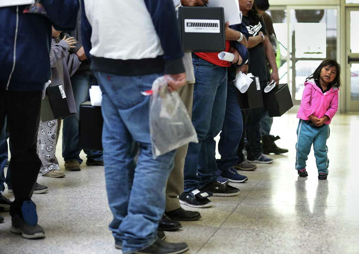 A young girl from Honduras, right, traveling with her father, looks at the line of 40 immigrants from Central America as they wait in line to get their bus tickets at the Central Bus Station in McAllen, TX, on Tuesday, Dec. 27, 2016.