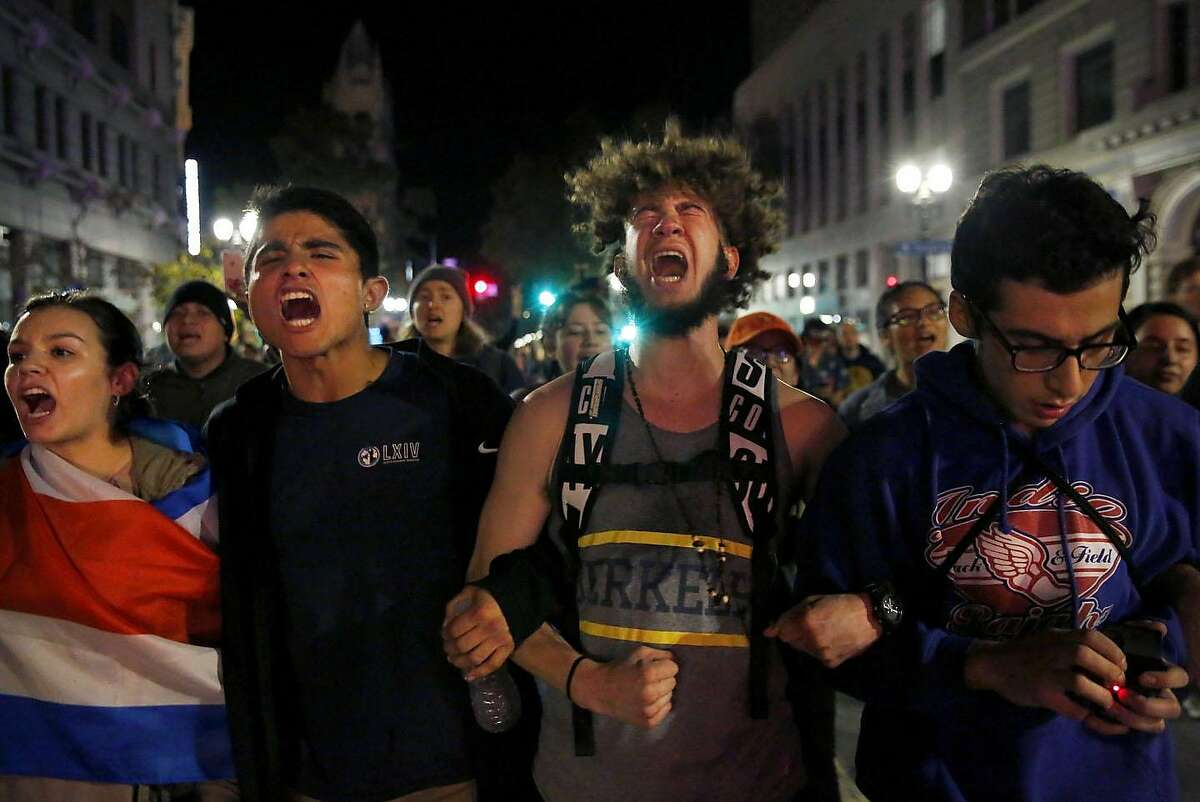 """Protesters from Berkeley chant """"not my president"""" as they march down Broadway during an anti-Trump protest Nov. 8, 2016 in Oakland, Calif., after the announcement that Republican presidential candidate Donald J. Trump won the presidential election."""