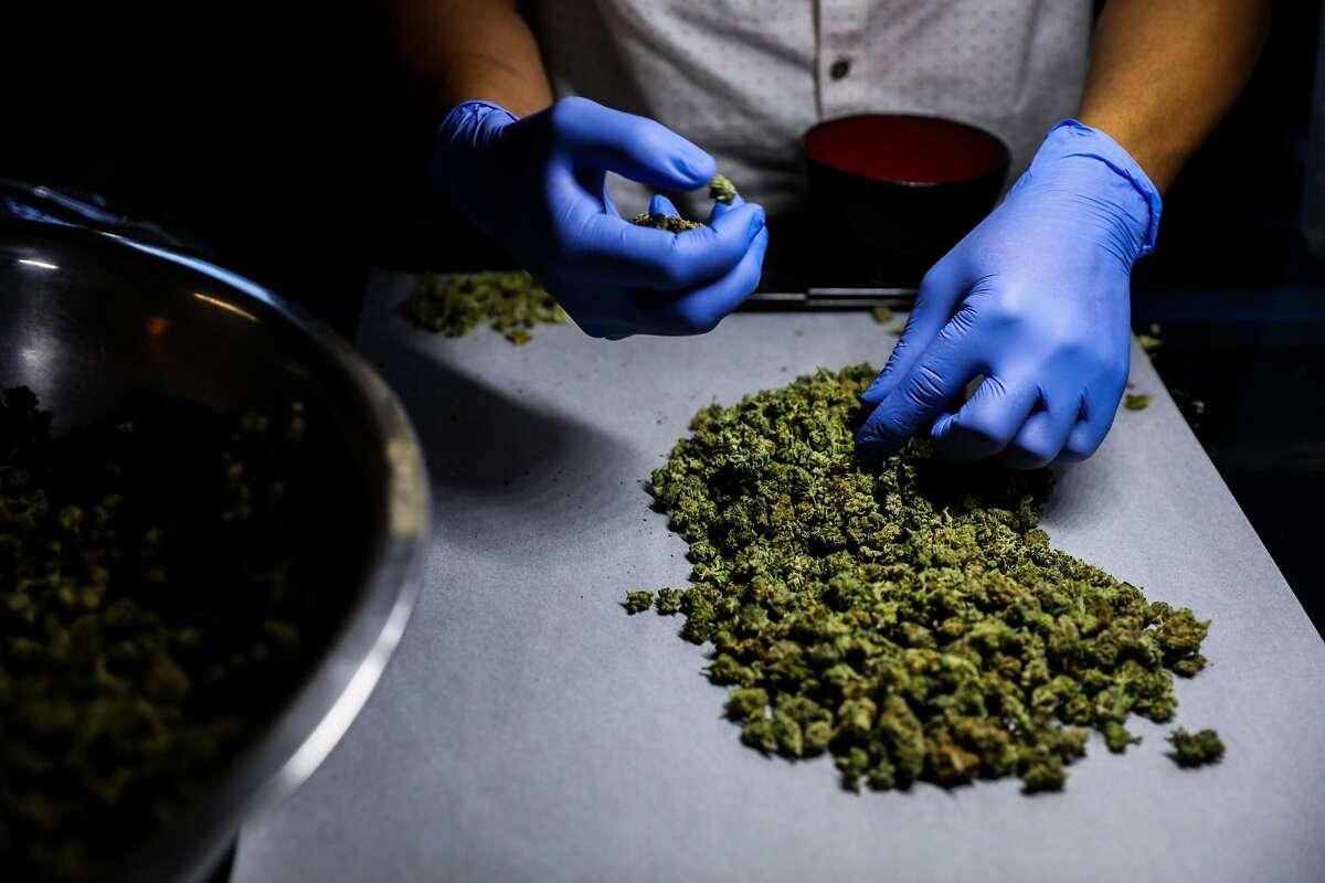 Employee Inmer Avalos sorts marijuana at cannabis dispensary, The Green Cross, in San Francisco, California, on Friday, Oct. 28, 2016.