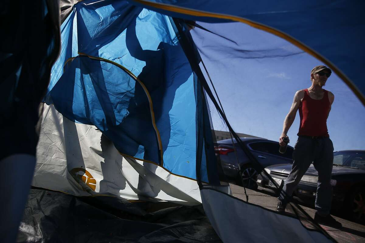 Katie Anderson is silhouetted in the morning light as she sets up her tent after the sidewalk had been cleaned by the Department of Public Works along Florida Street on Wednesday, October 19, 2016 in San Francisco, Calif.