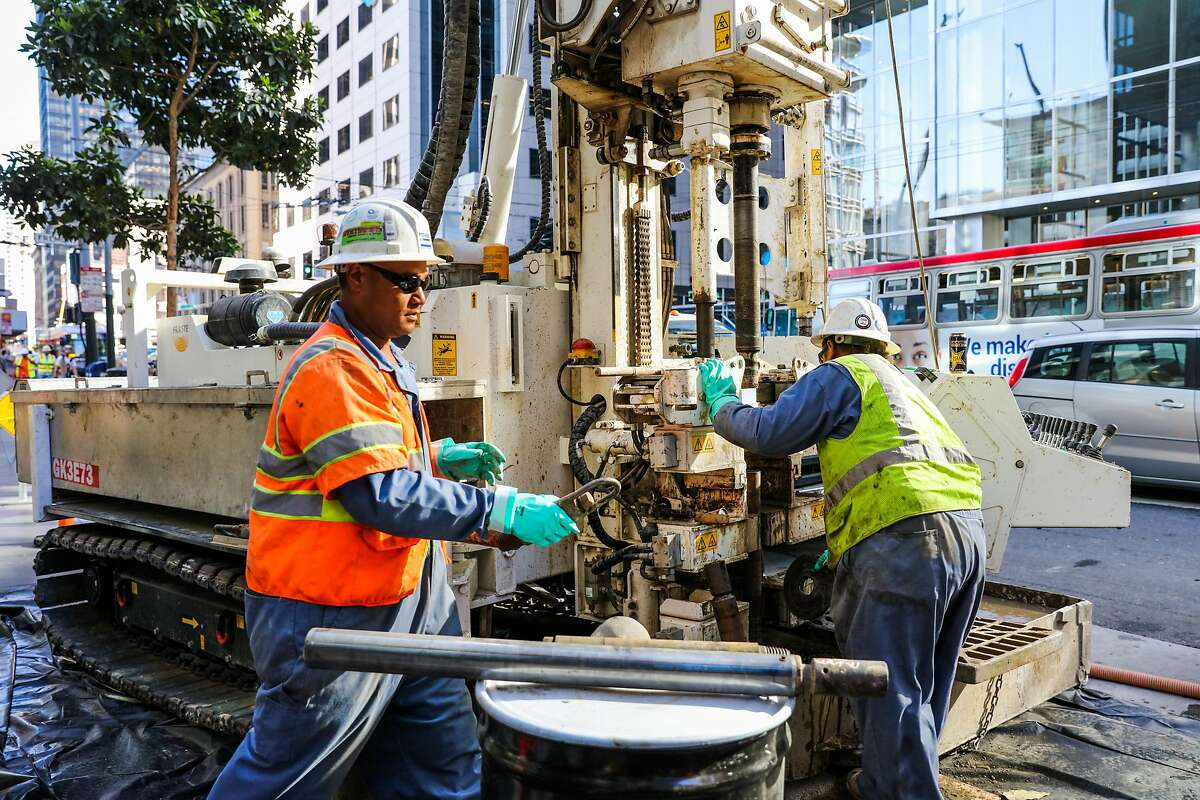 Workers Will Halai and Malakai Fakalolo (right) use a Fraste machine while doing tests soil levels outside the Millennium Tower, a residential building which is leaning, in San Francisco, California, on Monday, Sept. 26, 2016.