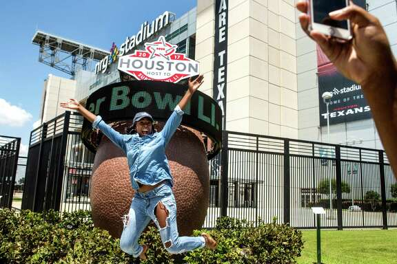 Brittney Lee, of Tomball jumps in the air as she poses for a photo next to the Super Bowl LI countdown clock outside NRG Stadium on Wednesday, Aug. 3, 2016, in Houston. Super Bowl LI will be played on Feb. 5, 2017, at NRG Stadium. ( Brett Coomer / Houston Chronicle )
