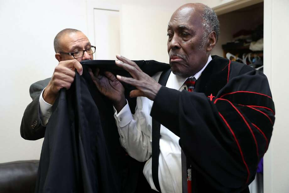 Reverend Ulysses Barton helps Gillette O. James, Pastor at Beth Eden Baptist Church, on with his robe before church service. Photo: Scott Strazzante, The Chronicle