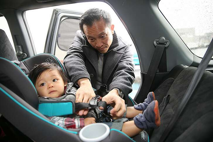 Assemblymember David Chiu (D-San Francisco) straps his 10 month old son Lucas into his rear facing car seat  on Friday, December 23, 2016,  in San Francisco, Calif.