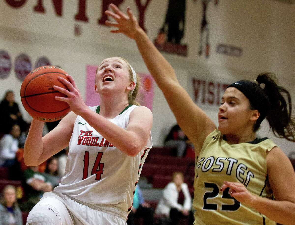 The Woodlands forward Emma Warnsman (14) shoots a layup past Foster forward Timara Taylor (25) during the second quarter of a high school girls basketball game at the Magnolia Holiday Hoop Fest Thursday, Dec. 29, 2016, in Magnolia. The Woodlands defeated Foster 60-37 in the semifinals of the golf bracket to advance to FridayÂ?'s final at noon.