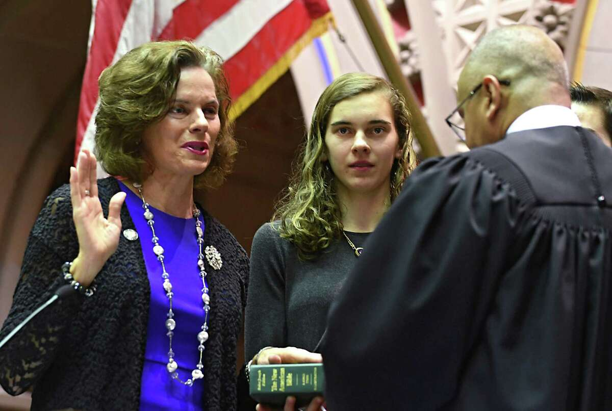 New York Assemblywoman Patricia Fahy is sworn in for another term administered by Judge William Carter in the Assembly Chamber of the State Capitol on Thursday, Dec. 29, 2016 in Albany, N.Y. Fahy's daughter Eileen Bequette, center, holds the bible.(Lori Van Buren / Times Union)